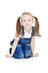 little smiling girl in blue jeans kneeling on the floor