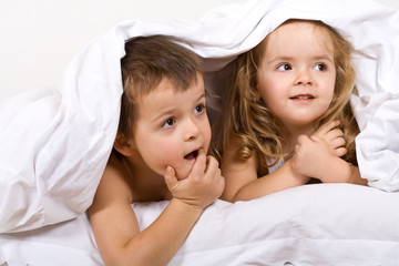 Kids playing under the quilt in bed