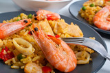 Fototapety Spanish paella on a dark plate with king shrimps