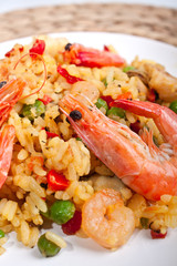serving of Spanish paella on s white plate with king shrimps