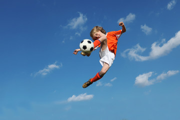 child playing football or soccer kicking ball