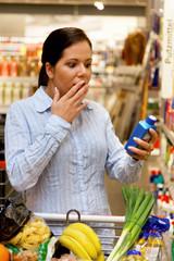 Frau mit Einkaufskorb im Supermarkt, erschreckt