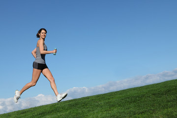 fit healthy woman exercising running uphill