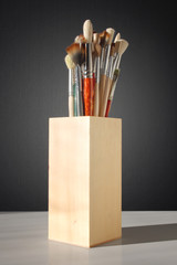 brushes for painting in a wooden glass on a table