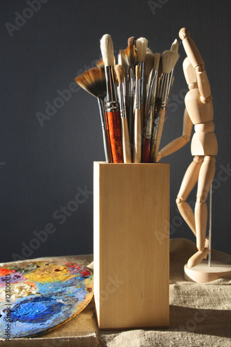 Art brushes in a wooden glass with a palette and model