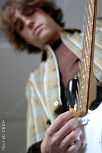 fourteen year old boy playing electric guitar