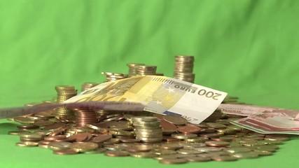 Geldscheine regnen auf Münzstapel