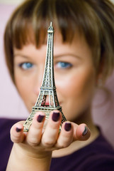 young woman holding statuette of Eiffel tower