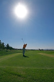 golfer teeing off into sun
