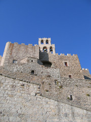 Walls of ancient castle with a bell tower