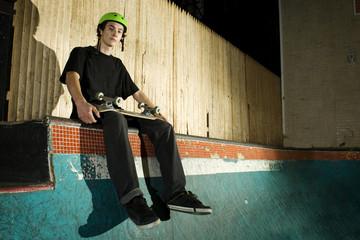 Skateboarder sitting on top of mini ramp