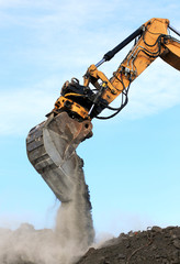 excavator arm and bucket scoop full of dirt at construction site