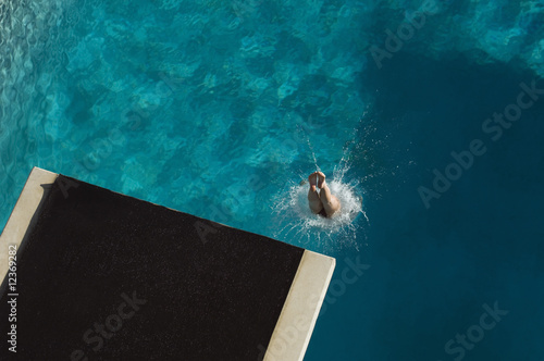 Young woman diving into swimming pool