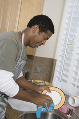 Mid-adult man washing dishes, smiling