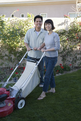 Mid-adult couple mowing lawn, smiling