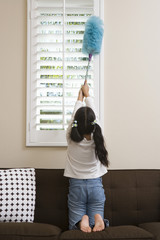 Girl 10-12 dusting window