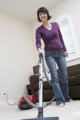Woman vacuuming floor in living room