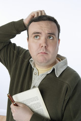 Portrait of mid-adult man holding pen and book, scratching his head