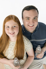Portrait of father and daughter holding bottles