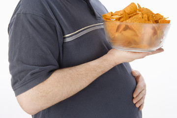 Mid-adult man holding glass bowl of potato chips, mid section
