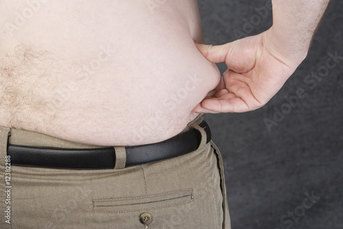 Overweight man pinching his Love Handles