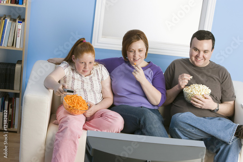 Overweight family watching television on sofa