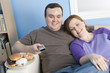 Overweight couple watching television on sofa