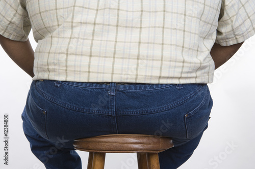 Overweight Man Sitting on Stool
