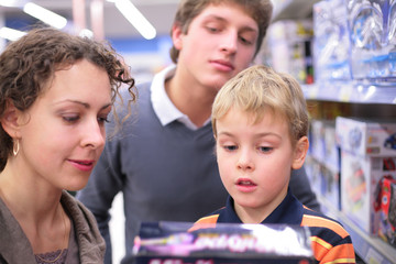 Father and mother with son with toy in shop