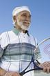 Senior man holding tennis racket