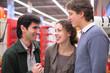 Three friends talk in shop