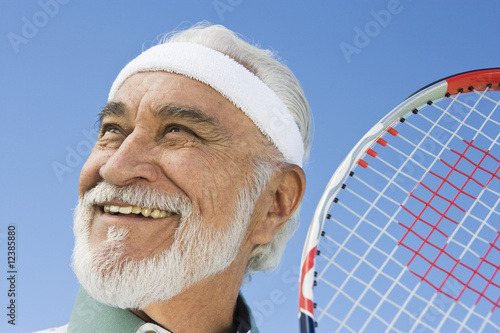 Senior man holding tennis racket