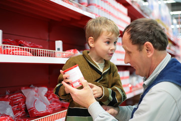 Grandfather and grandson choose conserve in food shop