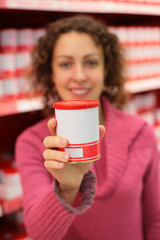 Young woman holds jar in food store