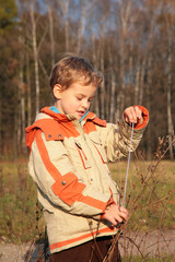 Boy in autumn wood with rope in hands
