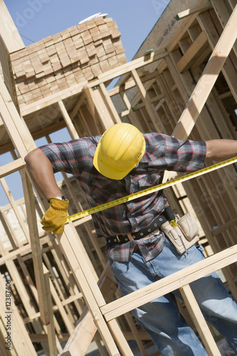 construction worker measuring building