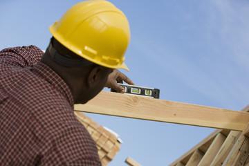 Construction worker using spirit level on building