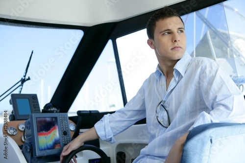 Young handsome man on a yacht boat interior