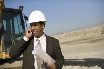 Surveyor using mobile phone on construction site