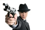 Classic mafia portrait, man with black suit and gun