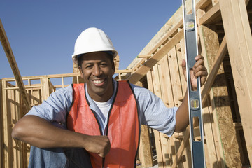 Construction worker holding spirit level on construction site
