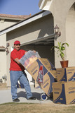 Delivery man holding cart with stack of containers