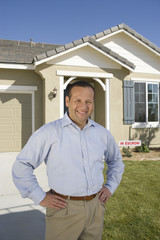 Portrait of mid-adult man in front of house, smiling