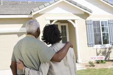 Middle-aged couple looking at house, back view