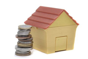 stack of coins iand a house solated in a white background