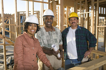 Two men and women with blueprints at construction site, portrait