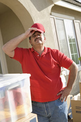 Mid-adult man putting on baseball cap, outdoors