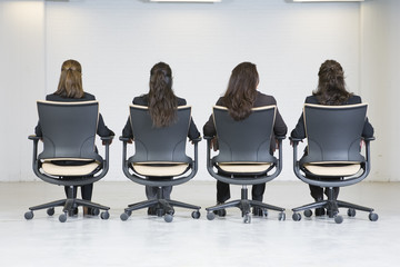 Rear view of business women sitting on office chairs.