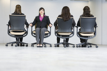 Business women sitting on office chairs.