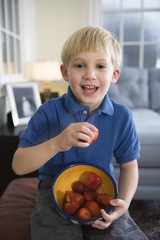 Portrait of boy eating strawberries..